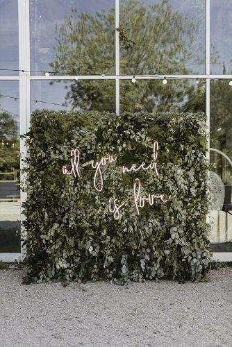 sage green wedding backdrop with romantic neon sign and greenery jenny demarco weddings
