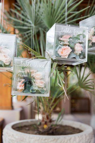 sage green wedding transparent cube with table setting signs greenery and roses inside maria sundin photography