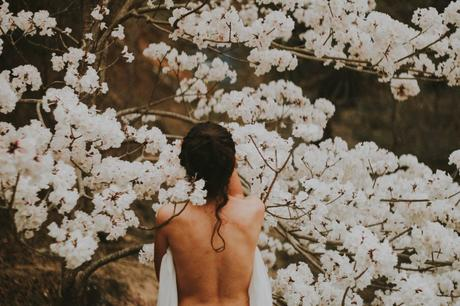 Viewed from the back and from the waist up, a nude person stands among a tree full of white flowers.