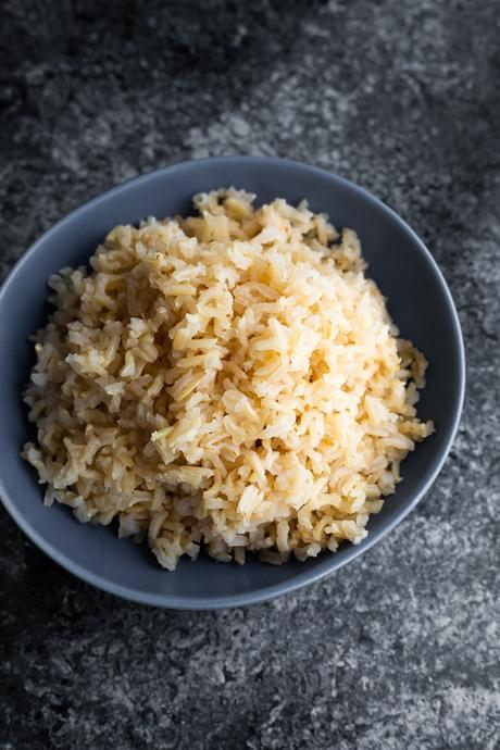 how to cook brown rice- showing cooked brown rice in blue bowl