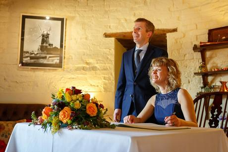 bride and groom pose for guests at their cley windmill wedding