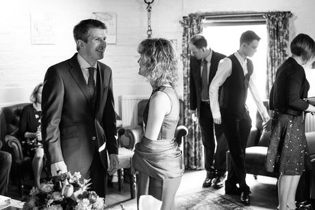 bride and groom laugh as their guests enter the ceremony