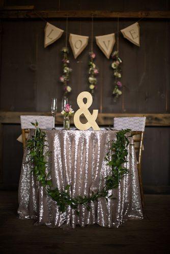 silver wedding decor ideas dark barn reception rustic sparkle tablecloth and greenery mari harsan studios