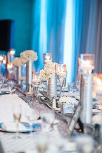 silver wedding decor ideas tablerunner with vaces candles and white flowers on reception with blue lighting natalie franke photography