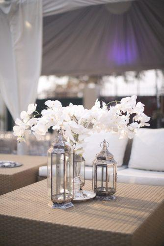 silver wedding decor ideas eclectic lanterns and white orchids on reception under the tent melissa jill photography