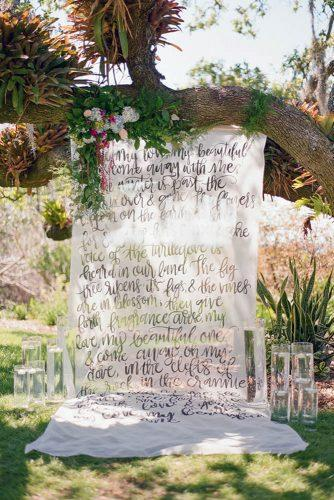 summer wedding trends outdoor ceremony backdrop with greenery and calligraphy signs the ganeys