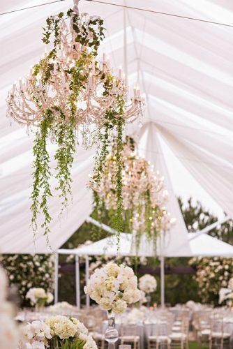 summer wedding trends reception under the tent with elegant chandelier and hanging greenery samuel lippke studios