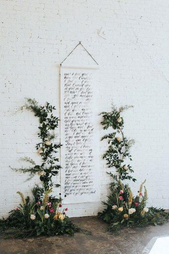 summer wedding trends ceremony backdrop with calligraphy signs and greenery and flowers jacobyphotoanddesign