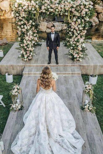 summer wedding trends outdoor wedding ceremony with greenery arch and white roses dmitry_shumanev