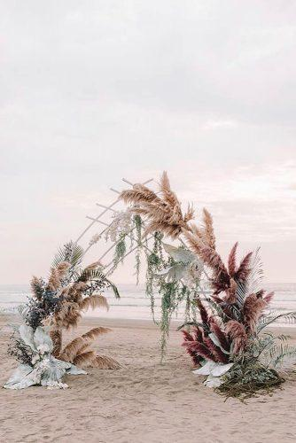 summer wedding trends bohemian beach ceremony with pampas grass and large leaves zhenyaswan