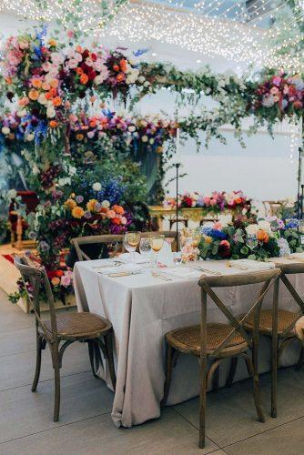 summer wedding trends evening lights on reception decorated with bright flowers michelle du toit