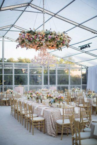 summer wedding trends reception under the tent with bridht flowers on table and haging installation john cain photography