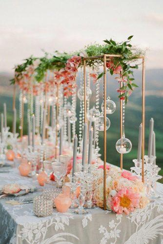 summer wedding trends tall centerpiece with coral orchids and peonies hanging crystals and candles flowers greg finck