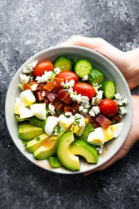hands holding a bowl of cobb salad