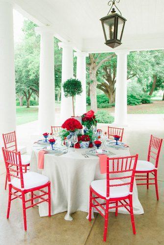 independence day wedding 4th of july outdoor reception round table with red chairs flowers and blue vases jennifer crenshaw photography