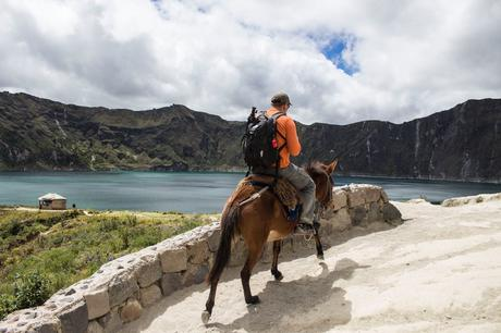 Man carrying a bag pack Riding a Brown Horse
