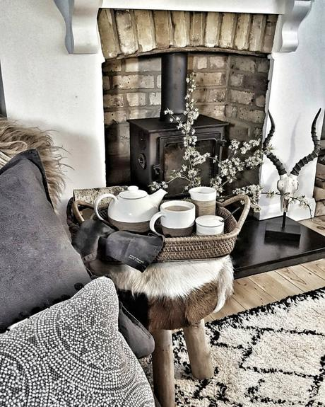 A rustic living room with a cast-iron fireplace.
