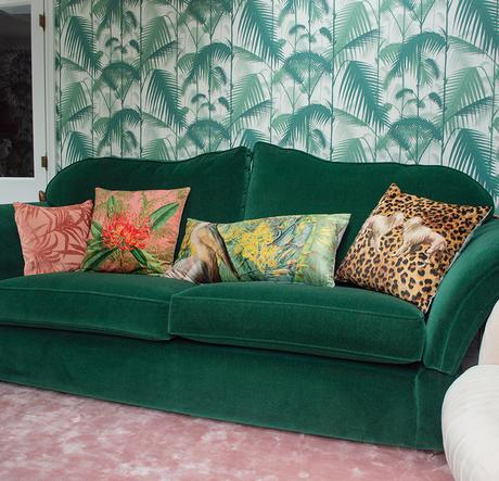 Colourful, patterned scatter cushions and green velvet sofa