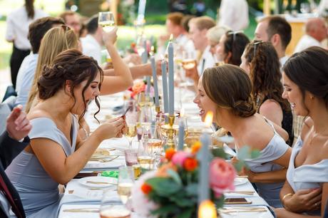 two bridesmaids laugh at a photo