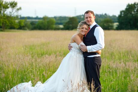 bride and groom pose in a field