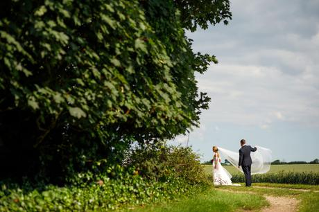 bride and groom pose for photos in a field