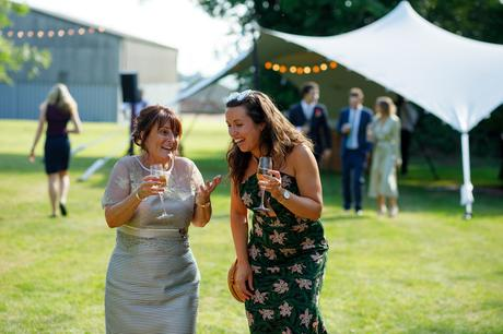 the brides mother and a guest walk into the marquee