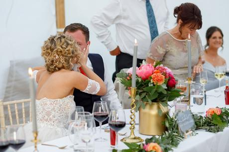 bride and groom kiss at the top table