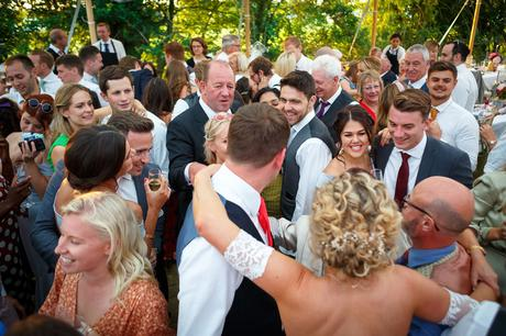 wedding guests smiling at the bride and groom on the dancefloor
