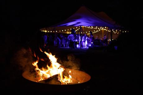 a firepit with the wedding marquee in the background