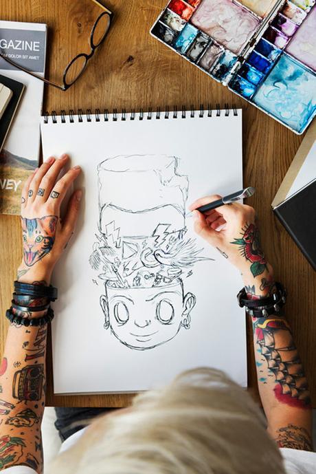 Women sketching with tattooed Hand