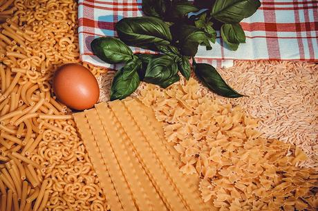 A picture of different shapes and types of dried pasta, garnished with a tomato and spinach leaf