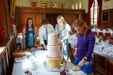 a friend applies the finishing touches to the wedding cake