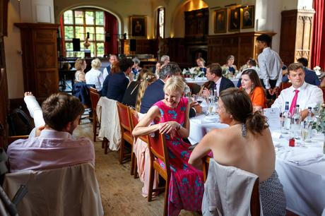 wedding guests chat in the dining hall at pembroke