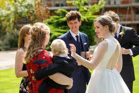 the bride and guests on the lawn at pembroke college
