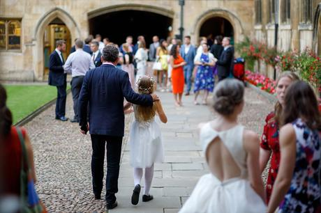 a bridesmaid walks with her father through pembroke college