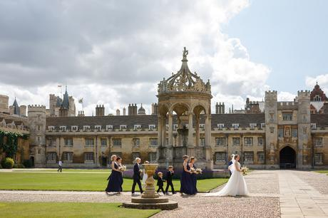 the bride walks in front of the fountain at trinity college cambridge