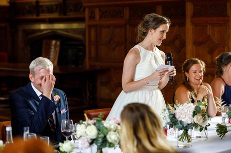 the groom laughs at the brides speech