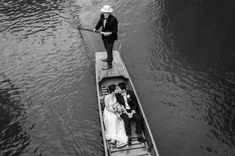 bride and groom kiss in a punt