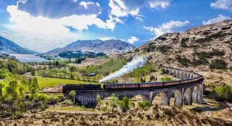 Enchanting Travels UK & Ireland Tours Glenfinnan Railway Viaduct in Scotland with the Jacobite steam train against sunset over lake