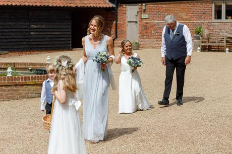 the bride walks across the courtyard at hautbois hall