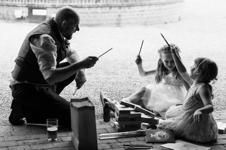 the groom casts spells with the flowergirl