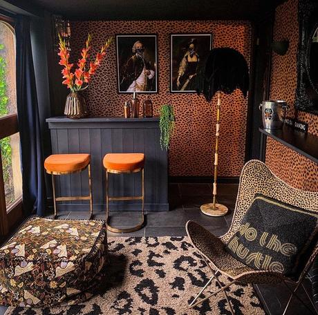 Maximalist home bar with leopard print wallpaper and leopard print home accessories.