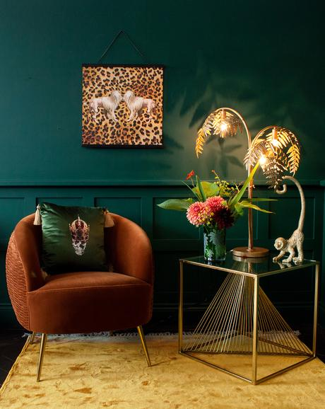 Moody green living room with leopard print wall art.