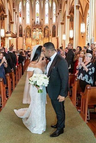 catholic wedding songs newlyweds kissing at the church