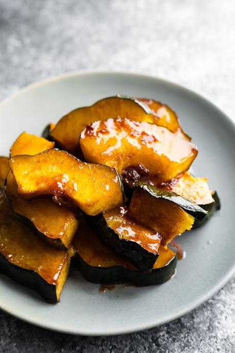 roasted acorn squash on gray plate with sticky glaze