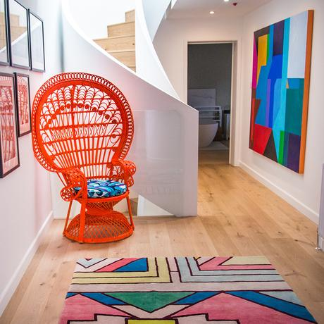 Spiral staircase with orange peacock chair