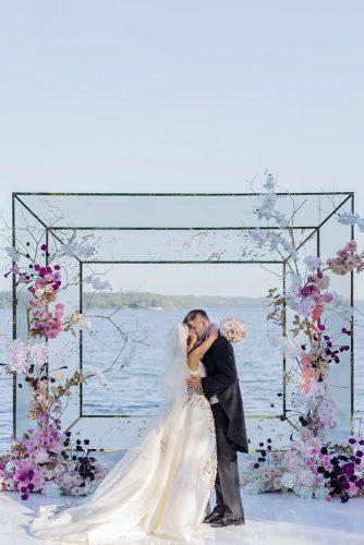 wedding colors 2019 groom and bride kissing geometric backdrop decorated with violet crocus and pink flowers roman_ivanov_weddings