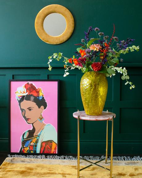 Colourful interiors - pink Frida print styled with yellow glass vase and velvet mirror