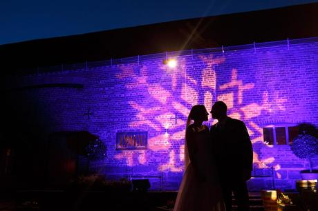 bride and groom pose outside curradine barns