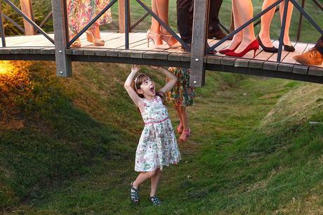 a cheeky girl under the bridge at a barn wedding